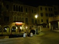 Street scene from Venice, Italy. Night, lamp post, canal, people sitting